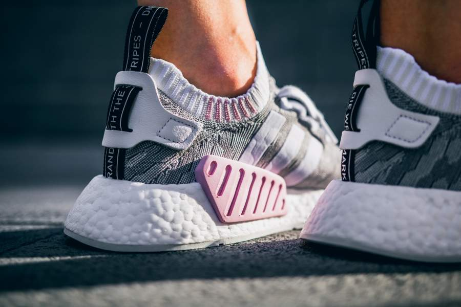 The adidas NMD R2 gets the glitch treatment in Womens sizes. Both mesh and  PrimeKnit colorways feature wonder pink 9ab0fac2a2e8